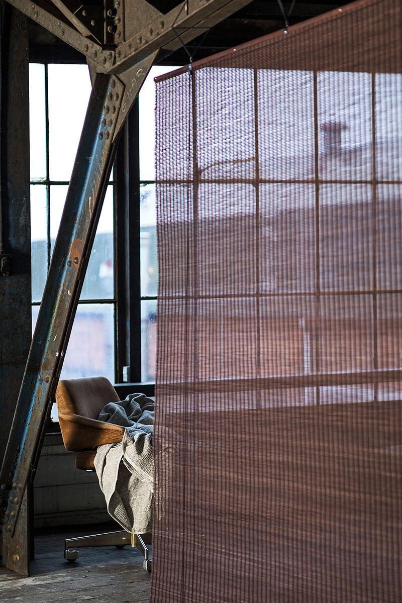 Løsthængende Bambus rullegardin i mørkebrun, bejdset brugt som rumdeler i studio.