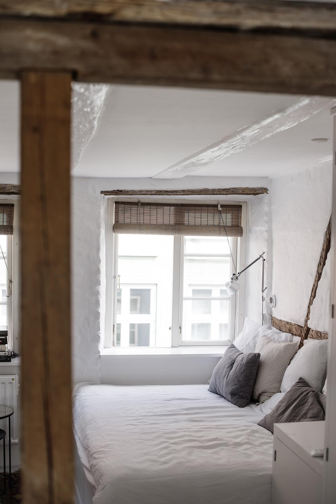Grå bejdset bambus rullegardin i soveværelse med synlige bjælker.